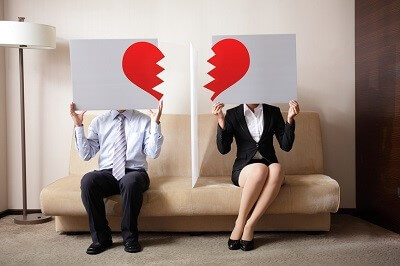 couple each holding half of a broken heart sign
