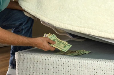man putting money under mattress